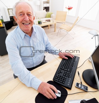 Portrait of a happy senior man using computer