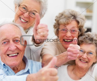 Group of happy older people showing thumbs up
