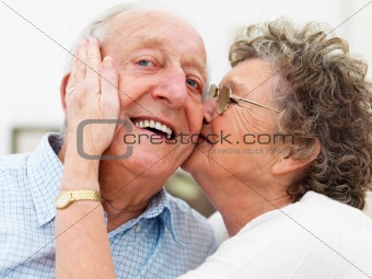 Happy senior woman kissing an old man