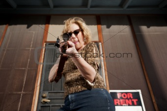 Woman on front porch with rifle