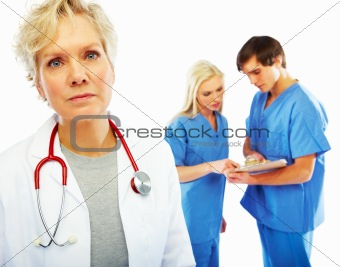 Senior female doctor with colleagues in back