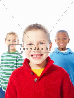 Portrait of happy young boy with two friends standing in background