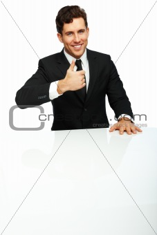 Closeup of young confident happy businessman in black suit smiling with his thumb pointing upwards