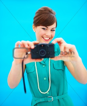 Closeup of attractive young woman using an antique camera standing against blue background