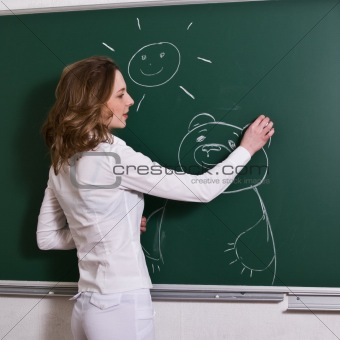 Young woman is drawing on a blackboard.