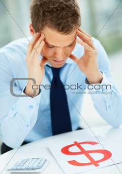 Closeup of young businessman sitting in the office and thinking about business problems