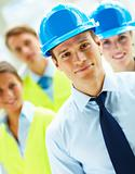 Portrait of young business man with hard hat with business people in background