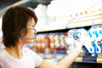 Closeup of a young woman purchasing grocery at the store