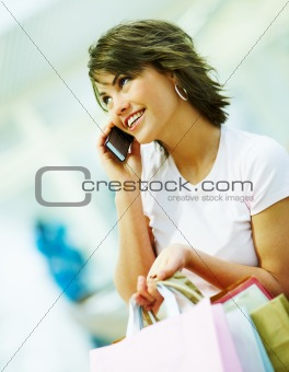 Portrait of a attractive young woman holding cellphone while carrying shopping bags