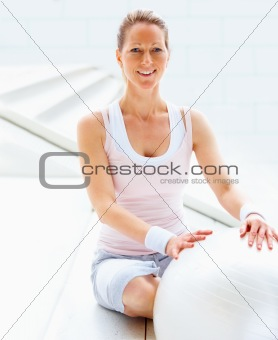 Portrait of happy mature woman sitting besides a fitness ball