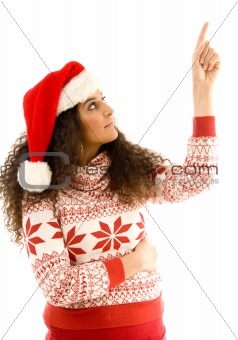 cute young woman wearing red christmas hat and pointing upwards