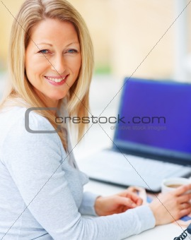 Closeup of young woman holding cup and laptop behind her