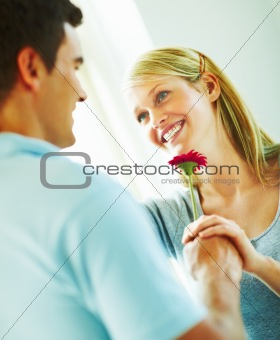 Happy young man handing over a flower to a young woman