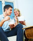 Portrait of a young couple eating using chopsticks