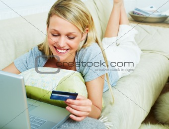Young woman lying on the couch and shopping from the internet using a credit card
