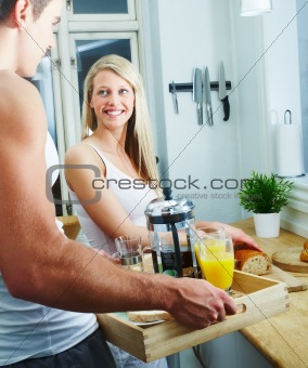 Happy young couple making breakfast together at home