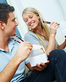Cheerful young couple eating from a takeaway container with chopsticks