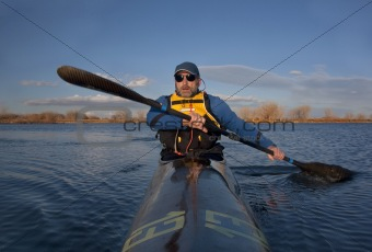 mature paddler in a narrow racing kayak