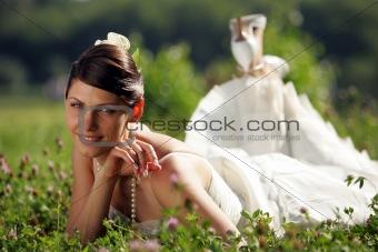 Smiling bride in summer meadow