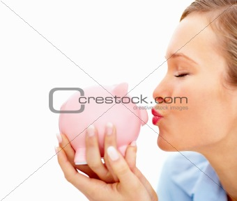 Attractive young female kissing piggybank and  copyspace