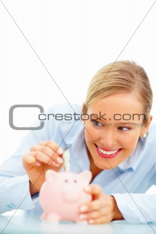 Young smiling woman putting money in the piggybank over white background