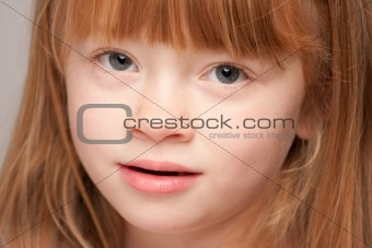 Portrait of an Adorable Red Haired Girl on a Grey Background.