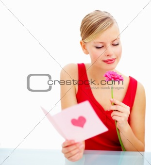 Happy young woman with valentine card and holding a flower against isolated background