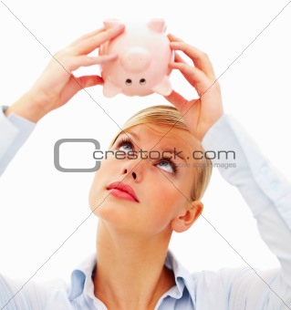 Closeup of attractive young woman holding piggy bank