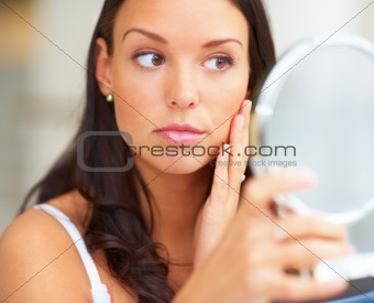 Beautiful young lady looking into a hand mirror