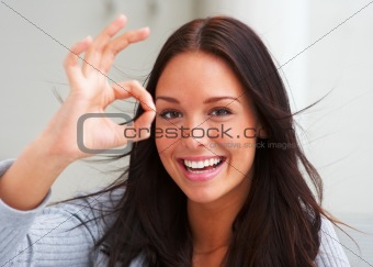Smiling young woman showing positive gesture