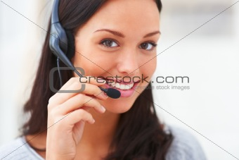 Happy young call center lady talking on headphones