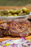 Grilled or barbecued pork meat with onion and pickles