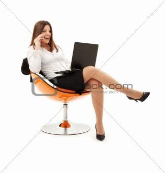 businesswoman in chair with laptop and phone