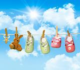 Baby shoes, pacifier and teddy bear on clothesline