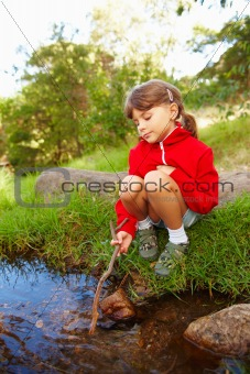Young girl sitting beside stream with a stick in her hand