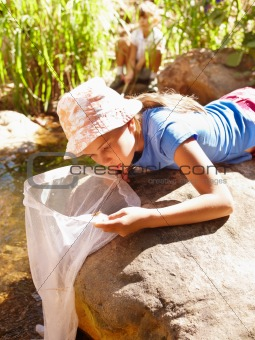Young girl lying on a rock by a stream and looking into her fishing net