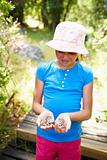 Cheerful young girl at a forest holding a butterfly