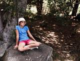 Closeup of young girl sitting alone on a rock by a tree at the forest