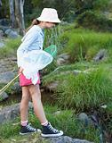 Young girl at the forest holding fishing net standing by the stream