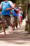 Group of children running over the wooden bridge at the forest