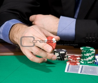 Hand with casino chip