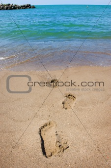 Footprints leading into a blue ocean