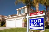 Blue Foreclosure For Sale Real Estate Sign in Front of House.