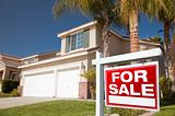 Red For Sale Real Estate Sign in Front of House.
