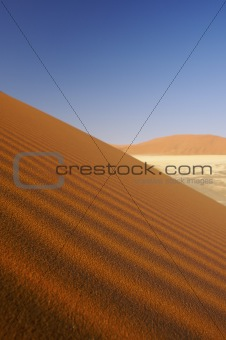 a desert landscape with dunes and a blue sky