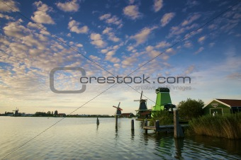 A colorful sunset in the Netherlands with windmills and canals