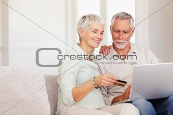Portrait of an old couple using their credit card to shop from the net using laptop