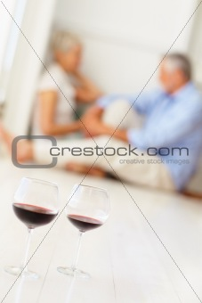 Two wine glasses on the floor with an old couple at the back