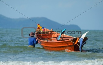 Fisherman taking his boat to sea
