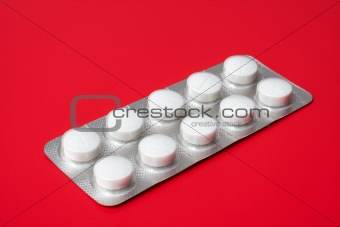 blister pack containing tablets on a red background